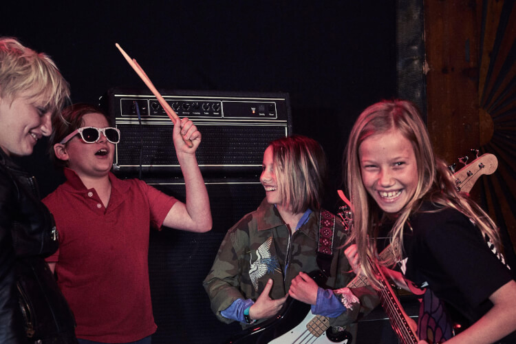 A group of School of Rock students smile in group music lessons