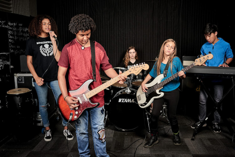 Students learning to play in School of Rock's music programs for teens