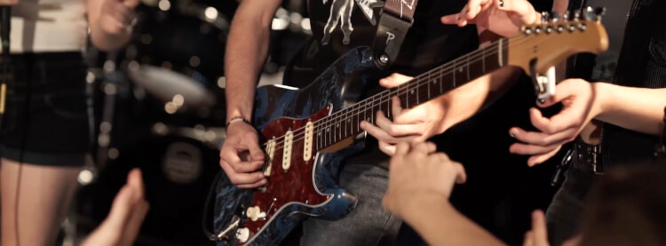 Teen playing guitar in School of Rock's Performance Program
